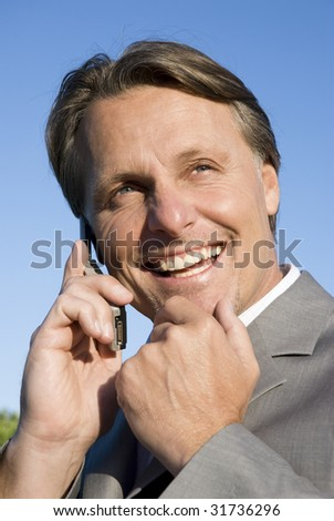 A handsome smiling forties businessman on cellphone. - stock photo