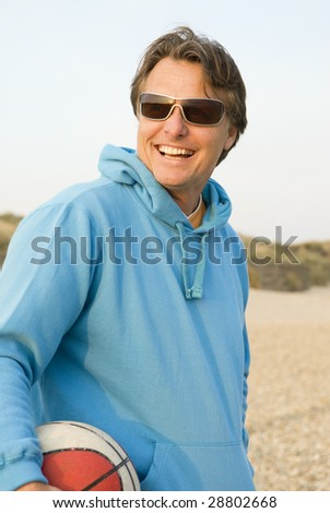 A handsome smiling forties man wearing sunglasses is having fun on the beach. - stock photo