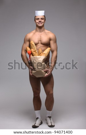 A handsome smiling man with bodybuilder physique holding a brown paper bag of baguettes concealing his loins, implied nude.
