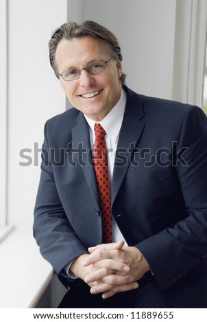 A handsome smiling professional man in a smart suit. - stock photo