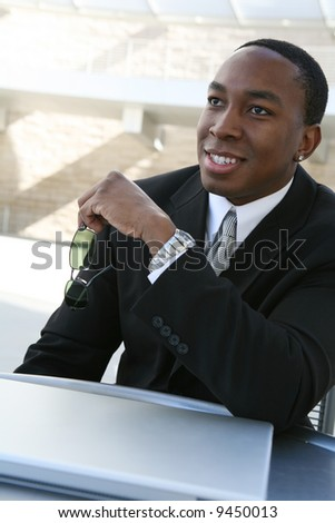 A handsome successful business man at a table with computer - stock photo