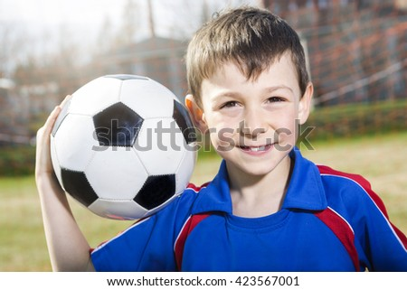A handsome teenager boy play football outside - stock photo