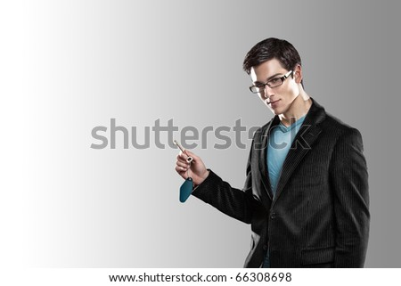 A handsome teenager standing in front of the camera in a smart suit holding a room key with a blank tag.