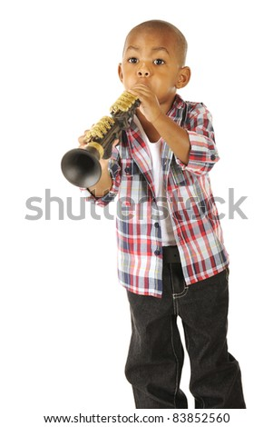 A handsome young African American tooting away on his toy clarinet.  Isolated on white. - stock photo