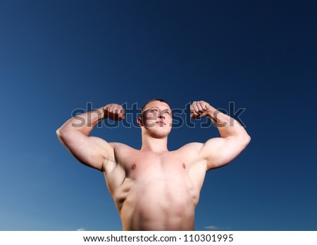 A handsome young and muscular man standing with his hands up - stock photo
