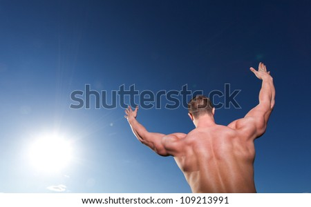 A handsome young athletic and muscular man standing with his hands up - stock photo