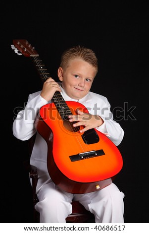 A Handsome Young Boy in a White Suit and with Guitar - stock photo