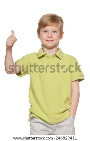 A handsome young boy shows his thumb up on the white background
