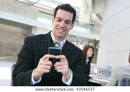 A handsome young business man texting on his phone at office building - stock photo
