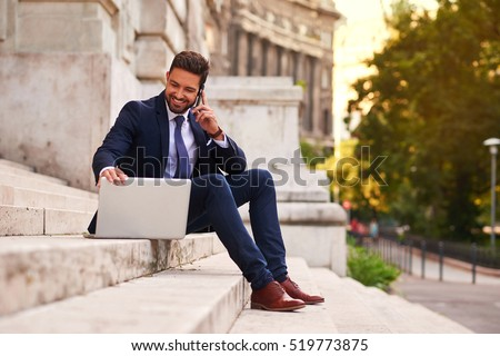 A handsome young businessman sitting next to his laptop on the stairs while talking on his phone