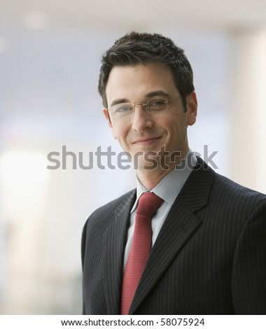 A handsome young businessman wearing glasses and smiling. Vertical shot.