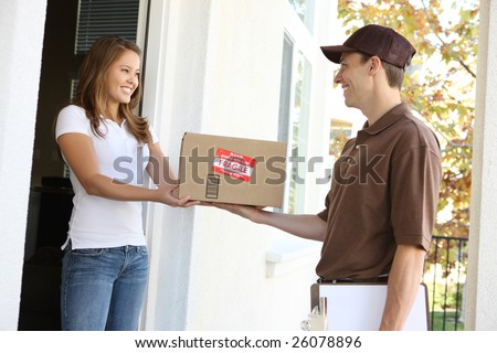 A handsome young delivery man delivering a package - stock photo