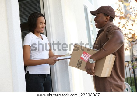A handsome young delivery man delivering a package to house - stock photo