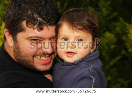 A handsome young father playing with his cute little son in the woods - stock photo