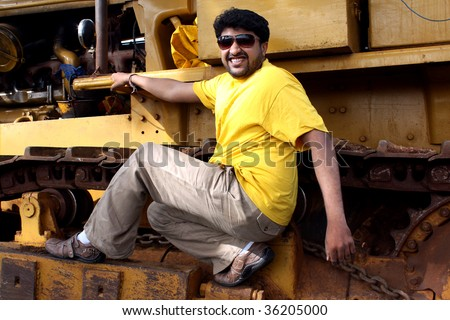 A handsome young Indian guy climbing up a huge bulldozer crane.