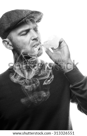 a handsome young man black and white with winter clothes and peaky blinder hat smoking isolated over a white background - stock photo
