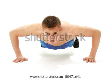 A handsome young man dressed in blue shirt making push-ups - stock photo