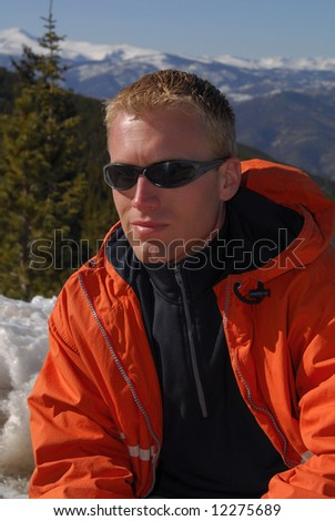 A handsome young man enjoying a day in the mountains - stock photo