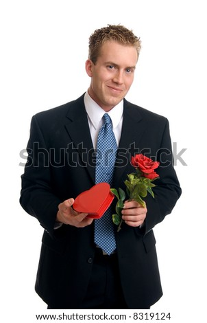 A handsome young man holding a rose and box of chocolates - stock photo