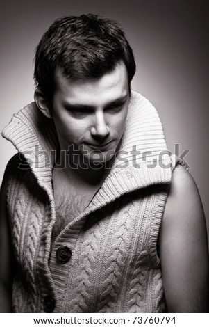 A handsome young man in a knitted sweater in dramatic lighting.