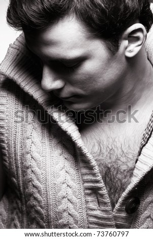 A handsome young man in a knitted sweater in dramatic lighting. - stock photo