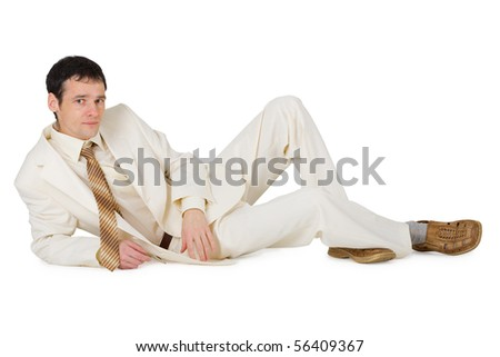 A handsome young man in a suit lying on a white background - stock photo