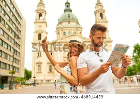 A handsome young man is feeling confused and looking at the map while his beautiful girlfriend is taking selfies at the St. Stephenâ??s Basilica in Budapest, Hungary.