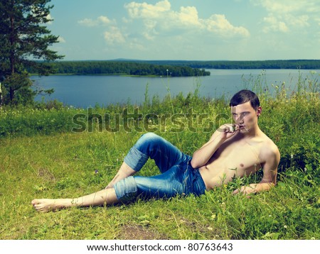 A handsome young man, lying on a sunny summer meadow - stock photo
