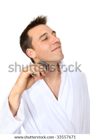 A handsome young man shaving with electric razor - stock photo