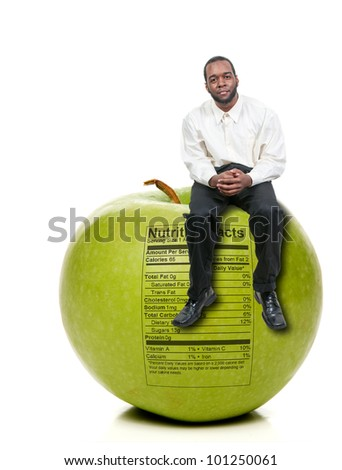 A handsome young man sitting on a green apple with a nutrition label