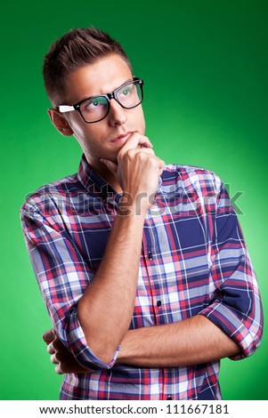 a handsome young man thinking on green background - stock photo