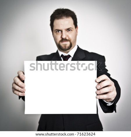 A handsome young man with a goatee beard shows paper - stock photo