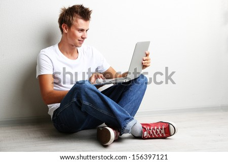 A handsome young man with laptop on grey background - stock photo