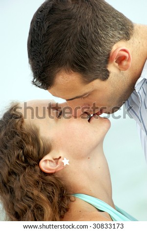 a handsome young man with short hair leans down to kiss a pretty woman with long curly hair - stock photo