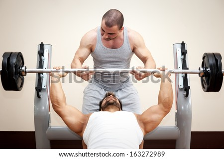 A handsome young muscular sports man doing bench press with a little help