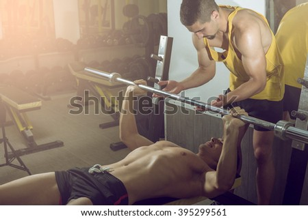 A handsome young muscular sports man doing weight lifting and gets help from his friend who is personal trainer. - stock photo