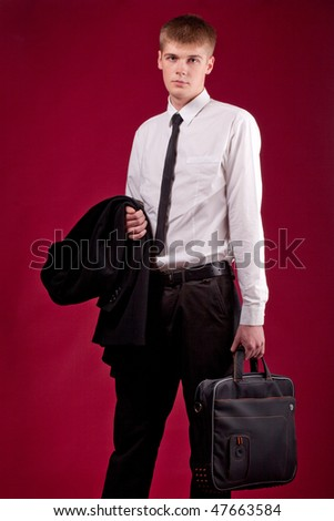 A handsome young student on a dark red background - stock photo