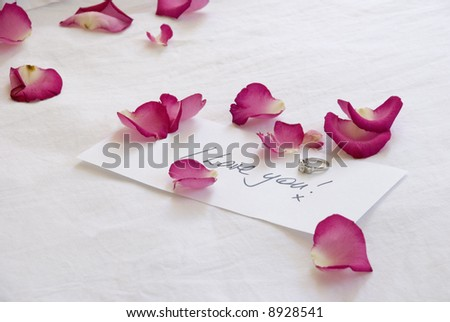 A handwritten love note and diamond engagement ring have been left on the bed amongst scattered pink rose petals - stock photo