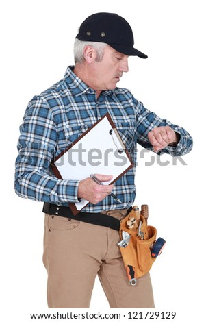 A handyman looking at his watch. - stock photo