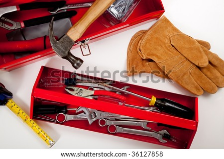 A handyman's tool box with assorted tools including hammer, measuring tape, pliers etc. - stock photo