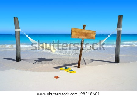 A hanging hammock, a wooden sign post , thongs and starfish on a deserted beach - stock photo