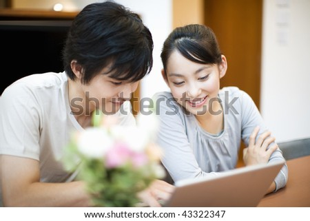 A happily young couple is watching PC together - stock photo