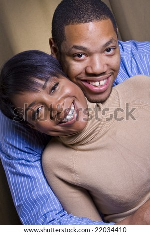 A happy african american couple smiling and embracing in front of a neutral background