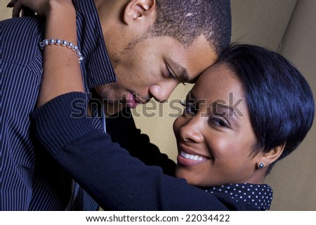 A happy african american couple smiling and embracing.  The man is looking at the woman and the woman is looking at the camera - stock photo