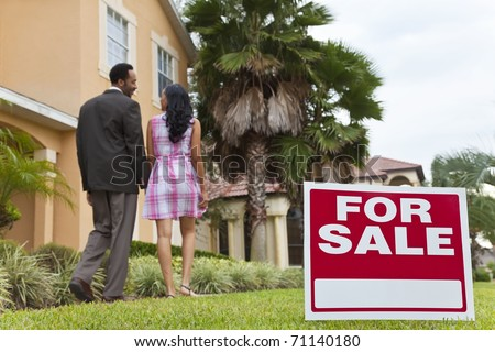 A happy African American man and woman couple house hunting outside a large house with a For Sale sign. The focus is on the sign. - stock photo