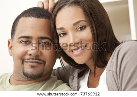 A happy African American man and woman couple in their thirties sitting at home - stock photo