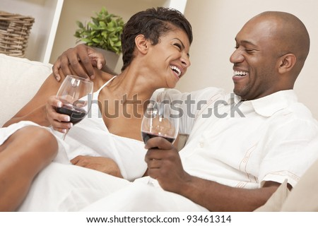A happy African American man and woman couple in their thirties sitting at home together laughing and drinking glasses of red wine. - stock photo