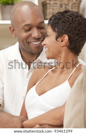 A happy African American man and woman couple in their thirties sitting at home together smiling looking at each other.