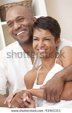 A happy African American man and woman couple in their thirties sitting at home together smiling. - stock photo