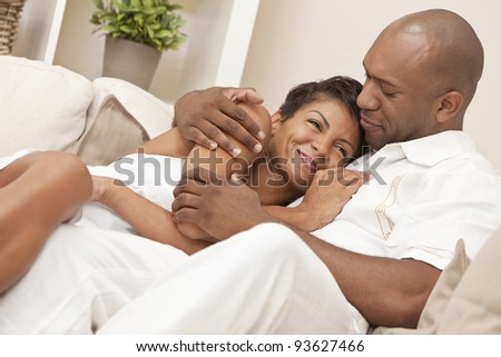 A happy African American man and woman couple in their thirties sitting at home together smiling and cuddling - stock photo